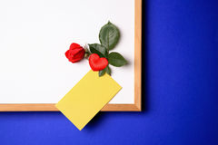 Whiteboard with yellow note. Whiteboard with empty yellow post-it note and magnet in the form of a hart and a rose.white-board with empty yellow post-it note and Stock Photo