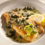 Whitefish with lemon. White fish with lemon and capris-olive oil dressing Royalty Free Stock Photo