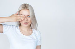 Whiteheaded young woman with beautiful blue eyes covering face Royalty Free Stock Photo