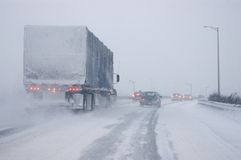 Whiteout Driving Conditions. A snow covered transport truck and multiple passenger cars driving in almost whiteout conditions Royalty Free Stock Photos