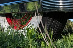 Whitewall, rear tire with chrome side wall on vintage car. Close up view of the rear tire of a vintage Cadillac parked in the grass with whitewall tires, red Stock Photos