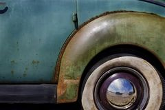 Closeup of whitewall Tires, fender and hubcap on Old Vintage Car with peeling paint Royalty Free Stock Image