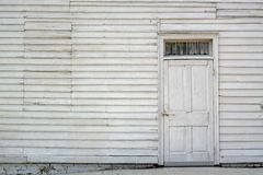 Whitewash Door. Whitewashed door on a white wall with window boarded up Royalty Free Stock Photos