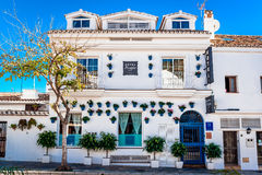Whitewashed building with blue flower pots in facades Stock Images