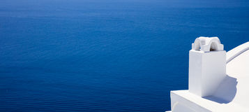 Whitewashed chimney in Santorini, Greece. Santorini island, Greece - White chimney on blue sea background Royalty Free Stock Photography