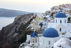 Whitewashed houses and blue dome church by the Aegean sea, Santoriniin Oia, Santorini, Greece. Famous blue domes in Oia village, royalty free stock photography