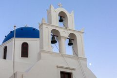 Whitewashed houses and blue dome church by the Aegean sea, Santoriniin Oia, Santorini, Greece. Famous blue domes in Oia village, royalty free stock photo