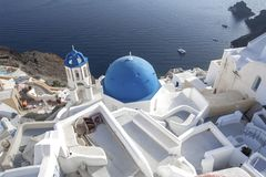 Whitewashed houses and blue dome church by the Aegean sea, Santoriniin Oia, Santorini, Greece. Famous blue domes in Oia village,. Santorini, Greece - Immagine royalty free stock photography