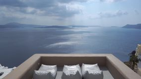 Whitewashed houses and church on cliffs with sea view and sunbeds in Oia, Santorini, Cyclades, Greece stock video footage