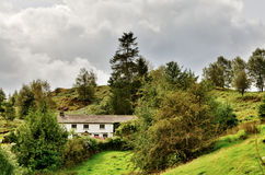 Whitewashed Lakeland Cottage on a Hillside Stock Images