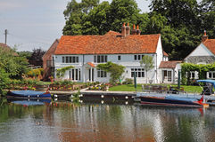Whitewashed Riverside House with Moorings Royalty Free Stock Photos