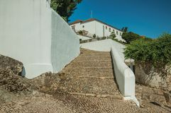 Whitewashed wall and cobblestone pathway with large stairs. Whitewashed wall and pathway made of rough stone with large stairs going up the hill, in a sunny day stock photo