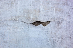 Whitewashed wall with the hole in the cracked plaster Stock Image