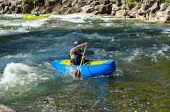 Blue canoe moving upstream. Whitewater canoe paddler paddling upstream royalty free stock images
