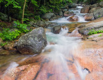 Whitewater at Franconia Notch. A stream rushes through the forest, splashing over boulders, down New Hampshire's scenic Franconia Notch Stock Photo
