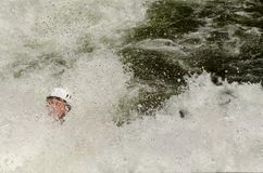 Whitewater kayak paddler. Covered with water spray in a turbulent river Royalty Free Stock Image