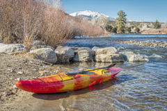 Whitewater kayak on river shore stock photo