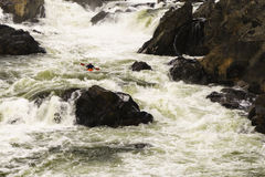 Whitewater Kayaker. POTOMAC, MARYLAND, USA - NOVEMBER 28, 2015: A man navigates the turbulent whitewater of the Great Falls of the Potomac River royalty free stock image