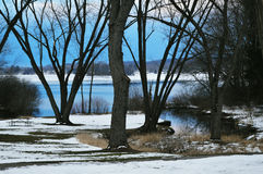 Whitewater Lake. In Whitewater, Wisconsin, part of Walworth County with trees, snow and water in the evening as the sun was going down royalty free stock image