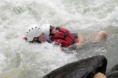 Whitewater Rescue. OCOEE, TENNESSEE - JULY 31: An unidentified rescue worker pulls an unidentified rafter to safety on July 31, 2010 on the Ocoee River in Royalty Free Stock Photography