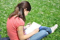 Whiteyoung student learns in a park. On the grass Royalty Free Stock Photo
