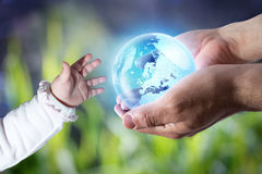 Give the world to the new generation. Whith baby hand and man hands royalty free stock photo