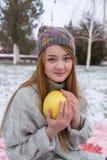 Whith de la muchacha del inconformista un pomelo en suéter y casquillo hechos punto Imágenes de archivo libres de regalías