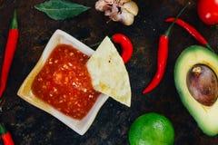 Whith mexicain chaud de Salsa les puces de nacho entourées par des ingrédients - tomates, poivrons de piment, chaux photos stock