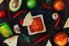 Whith mexicain chaud de Salsa les puces de nacho entourées par des ingrédients - tomates, poivrons de piment, chaux image libre de droits