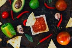 Whith mexicain chaud de Salsa les puces de nacho entourées par des ingrédients - tomates, poivrons de piment, chaux images stock