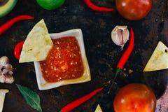 Whith mexicain chaud de Salsa les puces de nacho entourées par des ingrédients - tomates, poivrons de piment, chaux images libres de droits