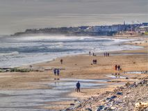 Beach view of Whitley Bay in North East England. Whitley Bay with wind whisking up the sea and dog walkers enjoying the sunshine Royalty Free Stock Photo