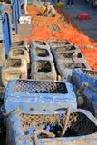 WHITSTABLE, GROSSBRITANNIEN - 15. OKTOBER 2017: Fischereikästen und bunte Fischernetze mit einem Fischer, der an seinen Netzen im Stockbild