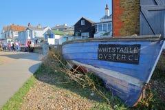 WHITSTABLE, GROSSBRITANNIEN - 15. OKTOBER 2017: Traditionelle hölzerne und bunte Häuser, die das Meer mit einem hölzernen Boot un Lizenzfreies Stockbild