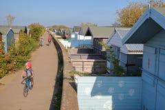 WHITSTABLE, UK - PAŹDZIERNIK 15, 2017: Rząd kolorowe drewniane budy wzdłuż drogi przemian i przegapiać morze Zdjęcie Stock