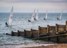 Whitstable Yacht Club New Years Eve. Whitstable, UK - Dec 31 2016  Members of Whitstable yacht club sailing in dinghy laser boats in front of the distinctive Royalty Free Stock Photos
