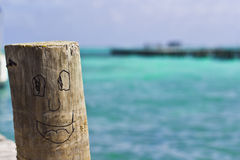 Whittled log. With a smiling face by the famous beach of San Pedro, Belize Stock Image