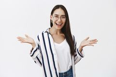 Who cares, let us have fun. Portrait of amused good-looking carefree female student in stylish striped shirt and glasses. Spreading palms aside while smiling royalty free stock photos