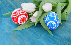 Who colored easter eggs with white tulips flowers on the blue Royalty Free Stock Images