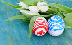 Who colored easter eggs with white tulips flowers on the blue Stock Photos