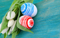 Who colored easter eggs with white tulips flowers on the blue Royalty Free Stock Photos