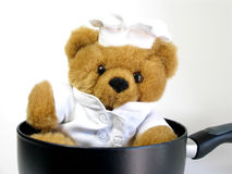 Who is cooking?. Teddy bear is in the saucepan. I wonder who is cooking royalty free stock photo