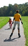 Who is faster?. Woman on rollers and girl on bicycle Royalty Free Stock Images