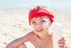 Who am I? Sunscreen (suntan lotion) is on hipster boy face before tanning during summer holiday. Royalty Free Stock Image