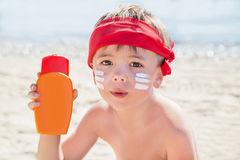 Who am I? Sunscreen (suntan lotion) is on hipster boy face before tanning during summer holiday on beach. Caucasian smiling child (kid) is holding container of Royalty Free Stock Image