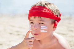 Who am I? Sunscreen (suntan lotion) is on hipster boy face  before tanning during summer holiday. Stock Image