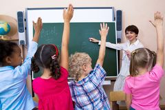 Who knows?. Image of pupils stretching their hands during the lesson Royalty Free Stock Images