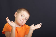 Who knows. Kid in orange shirt over dark background being at a loss Royalty Free Stock Image