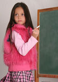 Who knows the answer. Young girl standing at chalkboard Stock Photo