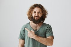 Who left rotten tomato in fridge, smells terrible. Portrait of displeasure easter curly-haired male with beard pointing. Left and frowning from displeasure and Royalty Free Stock Image